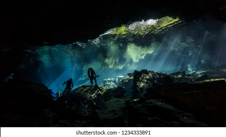 Divers play astronauts at the bottom of the Mexican cenote. Yucatán. Mexico.