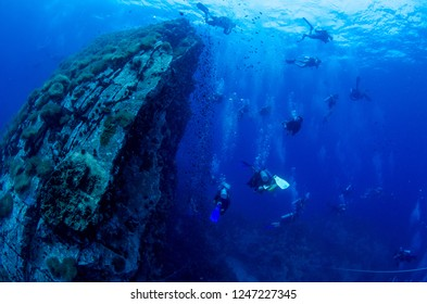 Divers swimming around south west pinnacle in Koh Tao