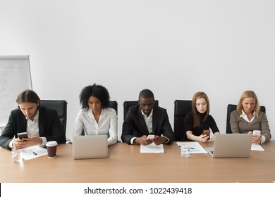Diverse african and caucasian office people using devices at team meeting, multiracial businessmen and businesswomen work with corporate gadgets sitting at conference table, business digitalization