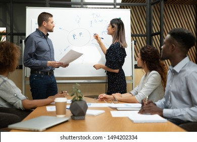 Diverse asian and caucasian professional coaches conference speakers drawing on whiteboard give business presentation in office, male female presenters team training worker group at corporate lecture