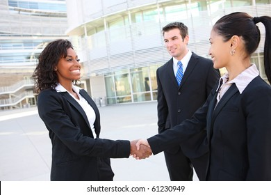 A diverse attractive man and woman business team handshake at office building