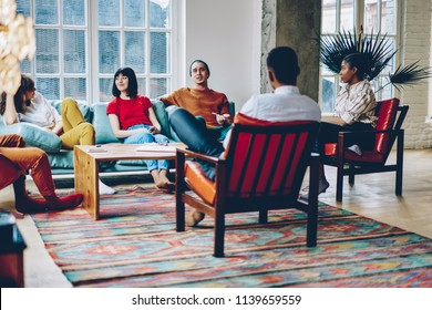 Diverse best friends dressed in casual wear communicating with each other enjoying leisure time in modern apartment.Multicultural young people have meeting to play game in stylish flat
