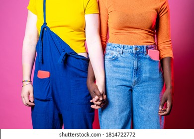 Diverse black and caucasian women holding hands - Two multi-ethnic women standing hand in hand against racism over pink background - diversity, inclusion, femininity concept