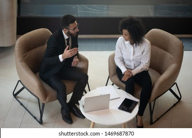 Diverse business partners discussing project, sitting in armchairs top view, negotiations or job interview concept, African American businesswoman and Caucasian businessman talking, sharing ideas
