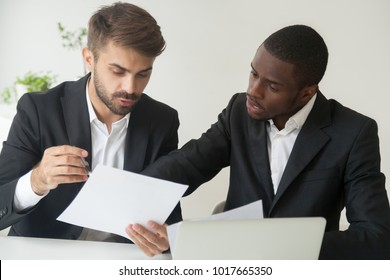 Diverse business partners in suits holding documents discussing reading contract terms, serious focused african and caucasian businessmen considering agreement deal talking about papers, paperwork