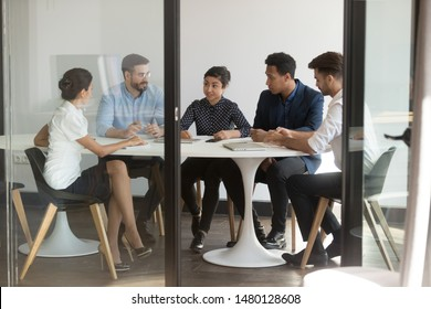 Diverse business people gather in boardroom negotiating planning future partnership view through opened glass door, company clients or workers listens hindu boss or team leader, formal meeting concept