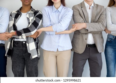 Diverse business people group standing holding hands, multi ethnic corporate team connected tied together as chain, unity help support concept, international cooperation and teamwork, close up view