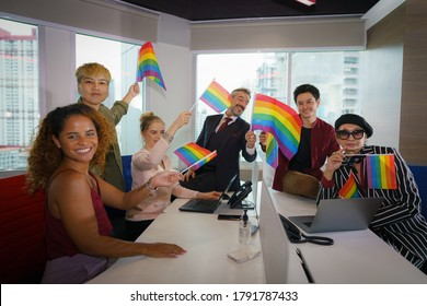 diverse business people (man, woman, gay, transgender, lesbian, asian, caucasian, african american, lgbtq) with rainbow flag on hand in business office working together as teamwork selective focused