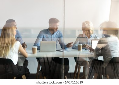 Diverse business people negotiate sit at conference table behind closed glass door at group private meeting, multi ethnic team staff employees talk at briefing discuss work in modern office boardroom