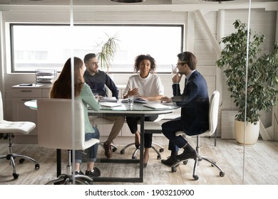 Diverse business people partners discussing project, contract terms, brainstorming in modern board room behind glass wall, colleagues sitting at table in office, talking, sharing startup ideas