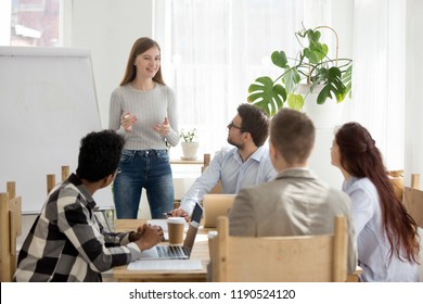 Diverse business people at seminar sitting in office. Young millennial leader boss female standing near whiteboard talking about development strategy to young colleagues clients at business meeting