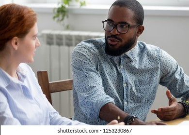 Diverse business people sitting at desk during meeting, black company owner talking with female investor discuss startup business plan. Multiracial colleagues take break having informal conversation