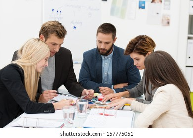 Diverse business team of dedicated young people sitting around a table in a meeting