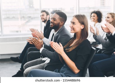 Diverse business team greeting speaker with applause and smiling, free space
