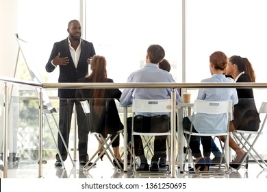 Diverse business team listening flipchart presentation of african manager coach mentor at corporate meeting training, black leader consulting people employees clients at workshop in modern boardroom
