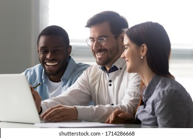 Diverse businessman and businesswoman laughing looking at laptop screen. African american man, woman and colleague happy smiling and enjoy free time. Teamwork at workplace concept.