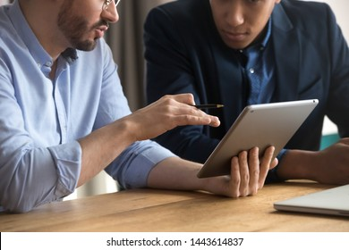 Diverse businessmen talking using digital tablet sit at office desk, male team two men working looking at tech device touchpad screen, corporate technology business apps concept, close up view
