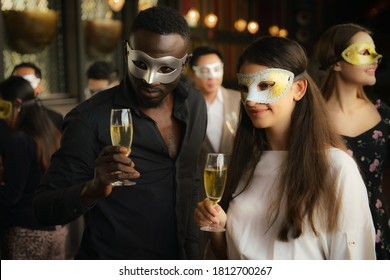 diverse businesspeople african american businessman and caucasian businesswoman having fun together in corporate mask party in business club and lounge