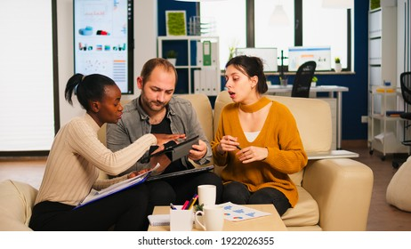 Diverse businesspeople analysing financial project during corporate meeting. Multiethnic employees group listening colleague sharing ideas discussing new marketing plan comparing data from tablet.