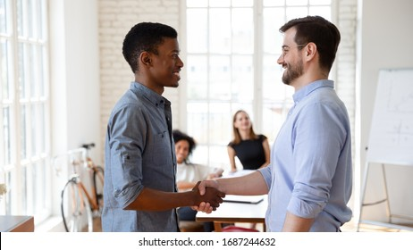 Diverse businesspeople gather in boardroom company boss handshake subordinate african staff member praising best employee of month, express gratitude for outstanding work, promotion and reward concept