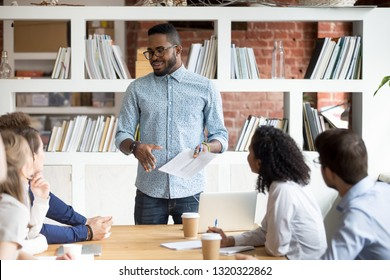 Diverse businesspeople gathered together at seminar for discussing new project, sharing information, thoughts and ideas in modern office. African coach presenting giving presentation for company staff