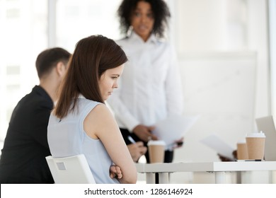 Diverse businesspeople in office during briefing focus on female worker feels guilty unhappy offended and frustrated having problem or disrespect from colleagues or made mistake, listens boss scolding