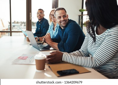 Diverse businesspeople sitting together in a row at an office table working on a laptop and discussing documents