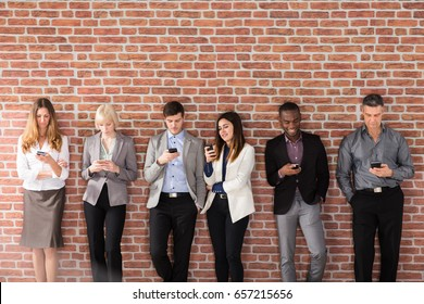 Diverse Businesspeople Standing Near The Brick Wall Using Smart Phone