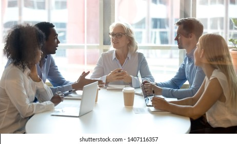 Diverse businesspeople talk at group negotiation, african partner offer idea discuss work at board meeting, multiracial professional team colleagues having conversation sit at conference office table