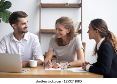 Diverse businesswomen businessman sitting at office desk use laptop reviewing documents. Cheerful workmates take brake joking or discuss project share thoughts business ideas feel good and satisfied
