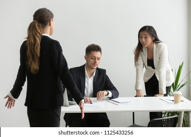 Diverse colleagues arguing about unpunctuality in office, coworkers looking at wristwatch blaming tardy employee for being late at meeting, bad time management, business team missed deadline concept