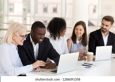 Diverse colleagues different race age businesspeople sitting together at desk in boardroom talking having pleasant informal conversation. Teamwork friendship at work between multiracial people concept