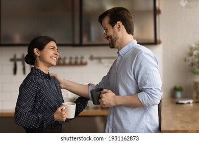 Diverse colleagues drinking coffee, chatting during break, enjoying pleasant conversation, Caucasian businessman executive congratulating Indian businesswoman with job promotion, touching shoulder