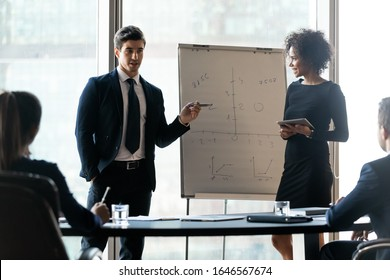 Diverse colleagues flip charts presentation new project in boardroom at company meeting. African american businesswoman and businessman auditors speaks with partners about business.