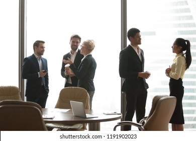Diverse colleagues having friendly conversation, drinking coffee standing near big office windows, employees talk or chat during break at corporate business meeting, workers enjoy casual communication