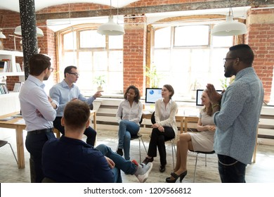 Diverse colleagues sit in circle have fun talking on business training with coach, multiethnic workers discuss ideas engaged in educational meeting, employees involved in teambuilding activity