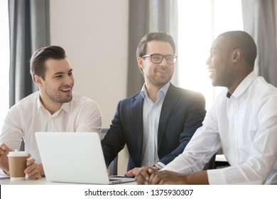 Diverse colleagues sitting at desk at meeting laughing having fun take break telling jokes anecdotes, warm relationships of multiracial business people, good work results successful teamwork concept