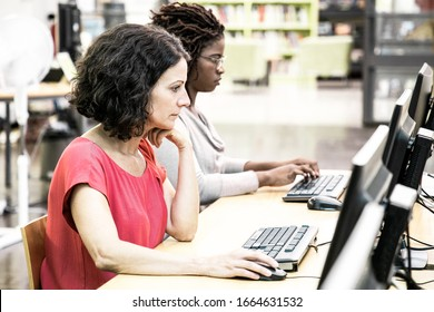 Diverse colleagues training to use corporate software in computer class. Women in casual sitting at table, using desktops, typing, looking at monitor. Corporate education concept
