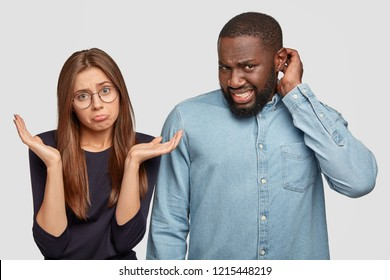 Diverse companions have clueless and displeased expressions, shrug shoulders, scratch head in bewilderment, cant find solution, pose against white background. Multiethnic couple express doubt