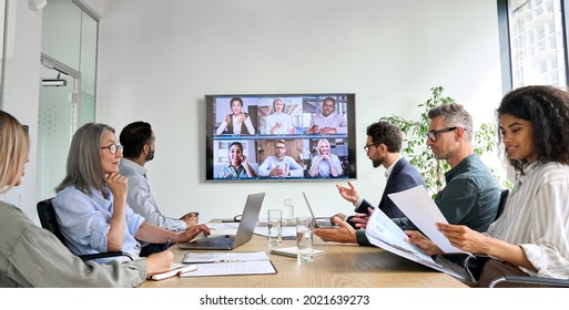 Diverse company employees having online business conference video call on tv screen monitor in board meeting room. Videoconference presentation, global virtual group corporate training concept.