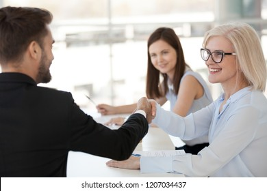 Diverse company workers handshake at briefing in office, smiling mature woman shake hand of millennial male colleague, get acquainted during business meeting, coworkers greeting introducing