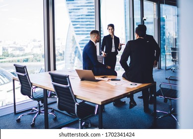 Diverse corporate professionals discussing business ideas during briefing meeting in office workspace, formally dressed executive managers have CEO conversation for talking and consultancy indoors