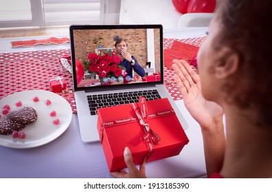 Diverse couple making valentines date video call on laptop holding gift and flowers and blowing kisses. online valentines day during quarantine lockdown.