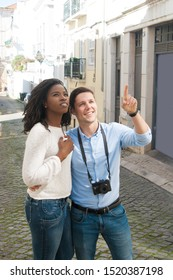Diverse couple of tourists looking at landmark. Young man and woman with camera standing in old town street, pointing finger and looking away. Sightseeing concept