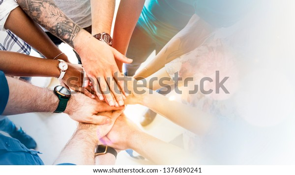 Diverse creative team stacking hands
