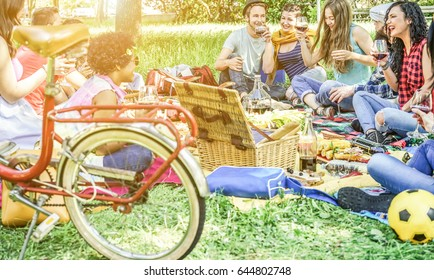Diverse culture friends making picnic on city park outdoor - Young trendy people drinking wine and laughing outside - Focus on man with hat and two girls next him - Youth concept - Contrast filter