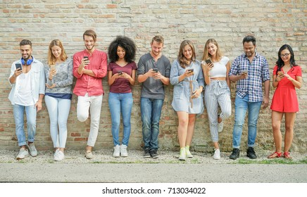 Diverse culture people using mobile smartphone outdoor - Happy friends having fun with technology trends - Youth, new generation addiction and friendship concept - Warm filter