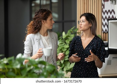 Diverse employees chatting during coffee break, walking in modern office, Asian businesswoman wearing glasses sharing ideas, discussing project with colleague, having pleasant conversation
