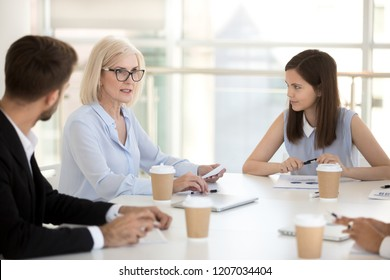 Diverse employees discuss project statistics at company business meeting, millennial employees listen to mature businesswoman talk, middle aged female boss negotiate with young coworkers at briefing