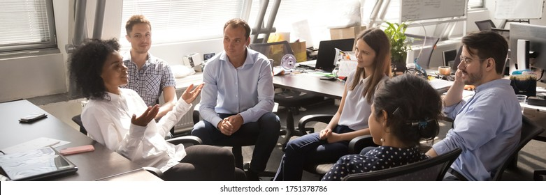 Diverse employees gathered brainstorming together in co working office, staff listen team leader, African woman share ideas, offer solutions concept. Horizontal photo banner for website header design